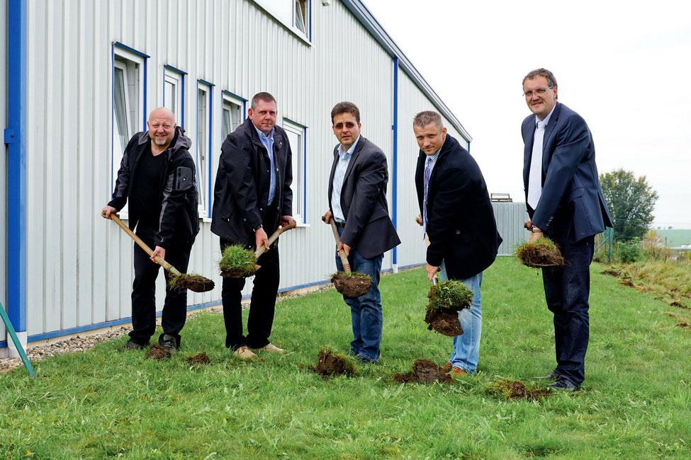 Der Planungsingenieur, der Bauleiter, der Geschäftsführer der Baufirma, der Bürgermeister und der Inhaber und Bauherr setzen gemeinsam zum Spatenstich an.