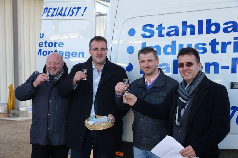 Der Planungsingenieur, der Inhaber und Bauherr, der Bürgermeister und der Geschäftsführer der Baufirma stoßen gemeinsam an
