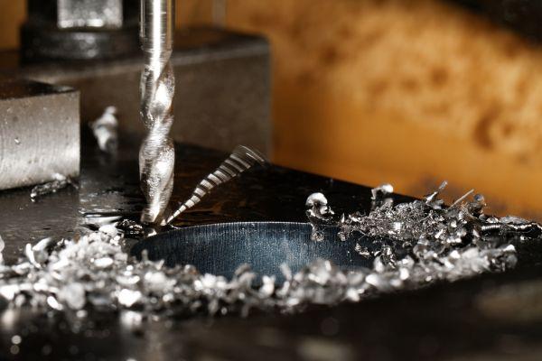 Ein Bohrer bohrt ein Loch und viele Metallspäne sind im Vordergrund zu sehen