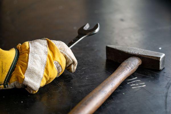 Ein Monteur hält mit einem Arbeitshandschuh einen Schraubenschlüssel und ein Hammer liegt daneben auf einer Werkbank