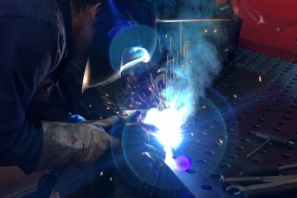 Ein Schweißfachmann mit einer Schutzmaske und Arbeitshandschuhen schweißt ein Metallerzeugnis