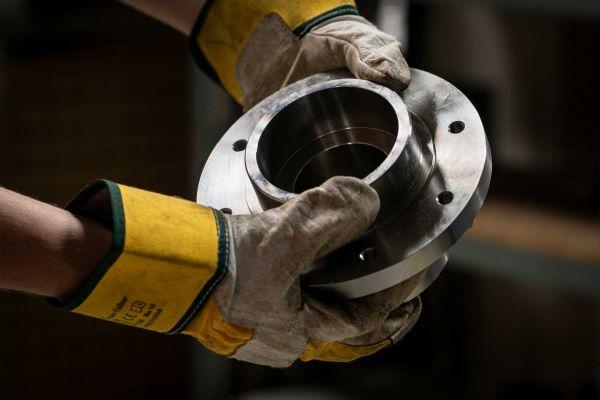 Zwei Hände in Arbeitshandschuhen, die ein Metallerzeugnis halten