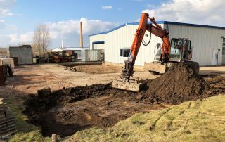 Ein Bagger hebt den Boden als Vorbereitung für das Fundament aus
